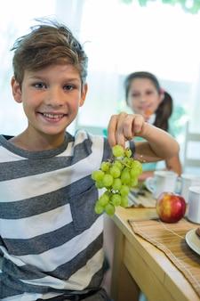 Jongen die een tros druiven houdt terwijl het hebben van ontbijt