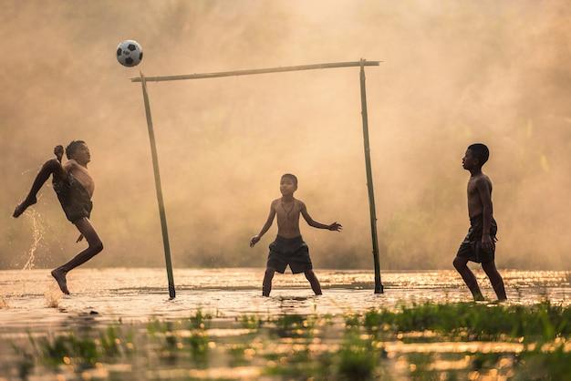 Jongen die een voetbalbal schopt