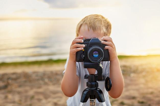 Jongen die foto's met een oude camera op het strand neemt