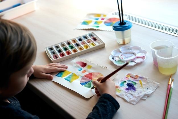 Jongen die foto's schildert met aquarelverf tijdens kunstles. leerling bij het tekenen met penseel. aquarel kleurenwiel en palet. kleurtheorie beginners hobby lessen.