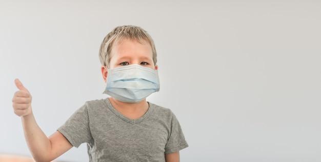 Jongen die gezichts wegwerpmasker draagt om virale infectie te voorkomen. stop het coronavirus