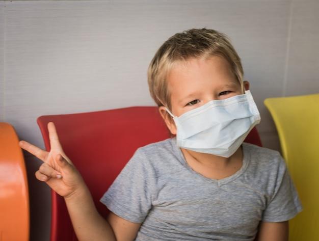 Jongen die gezichts wegwerpmasker draagt om virale infectie te voorkomen. virusbescherming