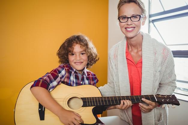 Jongen die gitaar leert spelen