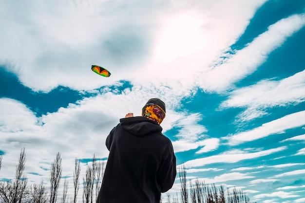 Jongen die grote vlieger vliegt op winderige dag