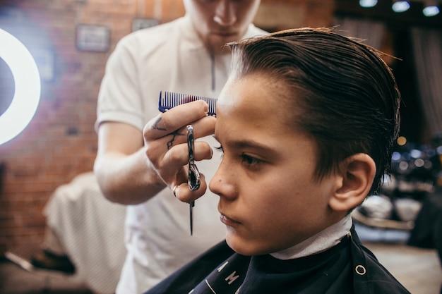 Jongen die haar haar heeft dat in een winkel van de hipsterkapper wordt gesneden