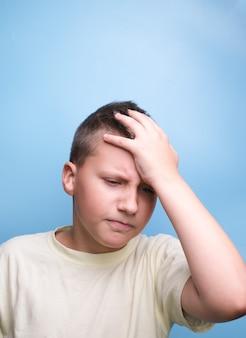Jongen die het hoofd bedekt met de hand die moe is, hoofdpijn, echte emotie toont.