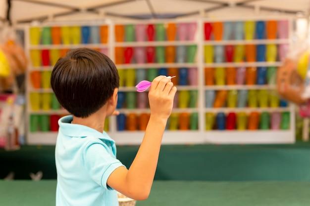 Jongen die het pijltjespel met veelkleurige ballons speelt bij markt.