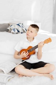 Jongen die hoe te leren ukelele te spelen