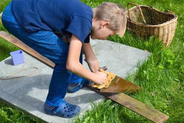 Jongen die hout zaagt. een jongen werkt in de tuin. kinderwerkplaats buiten