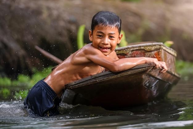 Jongen die in cannal dichtbij de drijvende markt van damnoen saduak zwemt