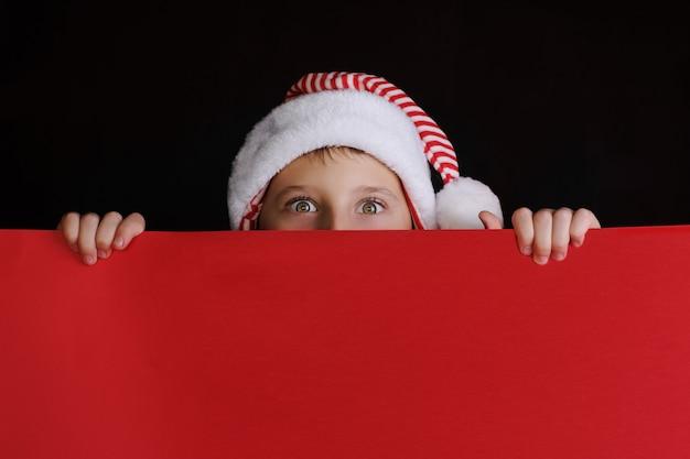 Jongen die in de hoed van de kerstman de rode lege banner voor kerstmisgroeten houdt. geïsoleerd op zwart