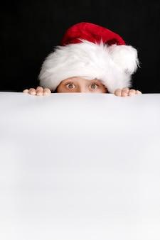 Jongen die in de hoed van de kerstman het witte lege aanplakbord voor kerstmisgroeten houdt. geïsoleerd op zwart
