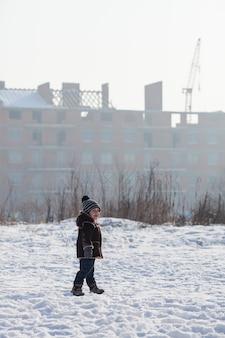 Jongen die in de winter loopt en naar de kraan kijkt op een bouwplaats