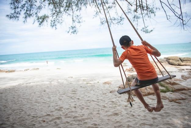 Jongen die in een schommeling op strand slingert