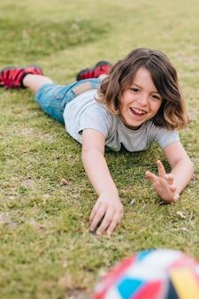 Jongen die in gras ligt en met bal speelt
