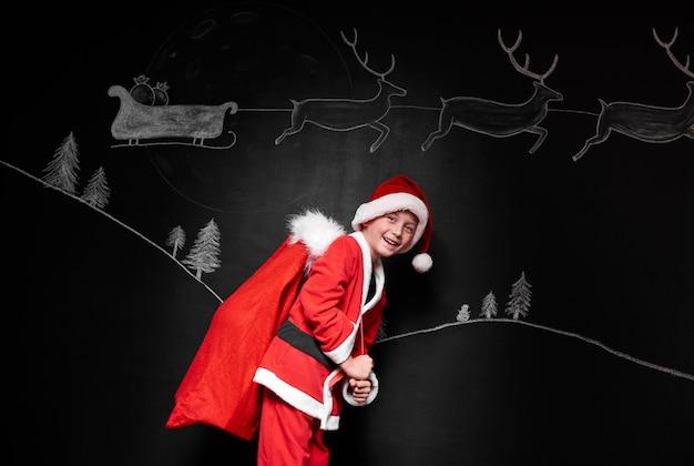 Jongen die in kerstmankostuum een zak met giften draagt