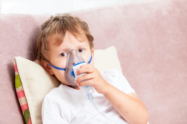 Jongen die inhalatie met een verstuiver thuis maakt