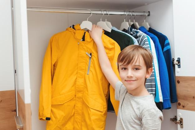 Jongen die jasje van hangerstribune neemt. kledingkast met kinderkleding.