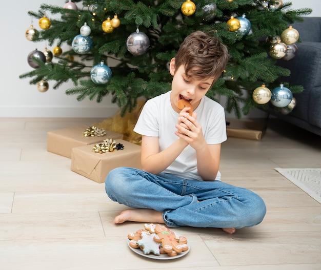 Jongen die kerstpeperkoek eet bij de kerstboom in de woonkamer