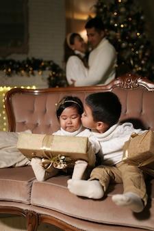 Jongen die kleine vrouw kust en een gift geeft terwijl hij op de bank bij de boom zit