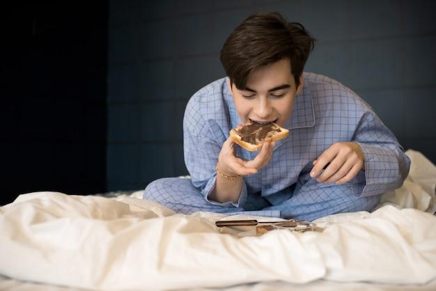 Jongen die knapperige toost in bed eet