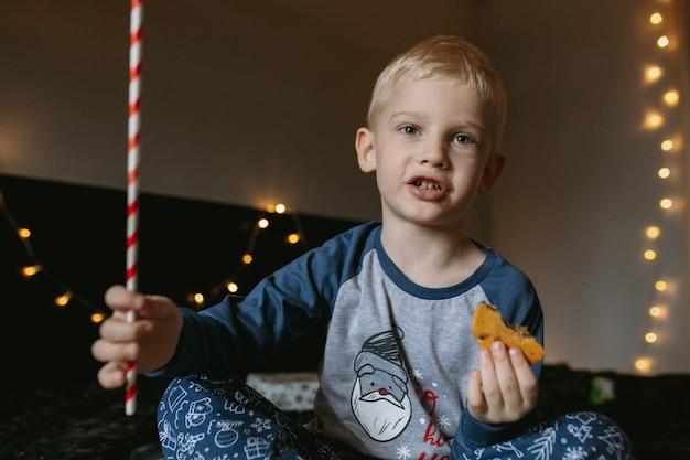 Jongen die koekjes eet en droomt van cadeautjes voor kerstmis met een rietje als een toverstaf