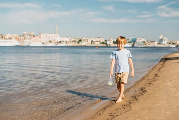 Jongen die langs kustlijn loopt