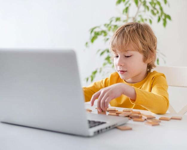 Jongen die laptop en speelgoed thuis met behulp van