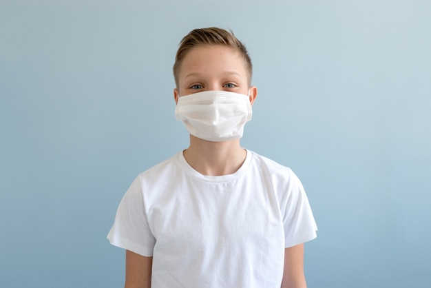 Jongen die medisch masker binnen draagt