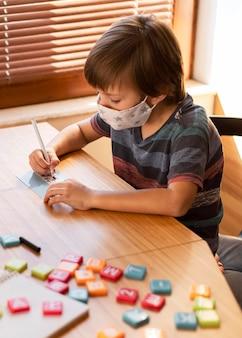 Jongen die medisch masker draagt tijdens zijn online lessen