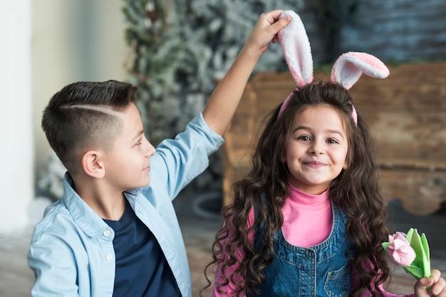 Jongen die meisje in konijntjesoren bekijkt met tulp