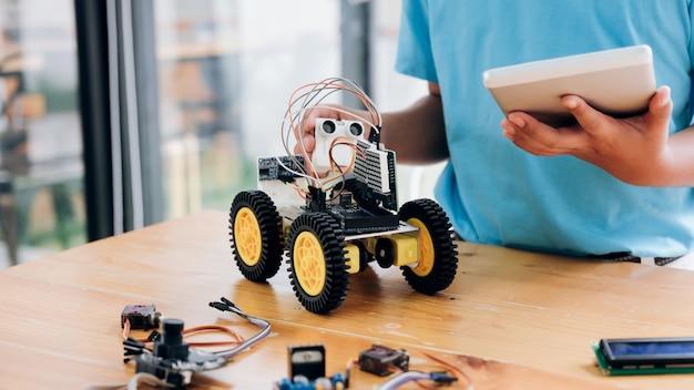 Jongen die met de computer van tabletpc elektrisch speelgoed programmeert en robots bouwt.