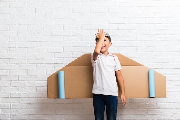 Jongen die met de vleugels van het kartonvliegtuig op zijn rug spelen die de oplossing realiseren