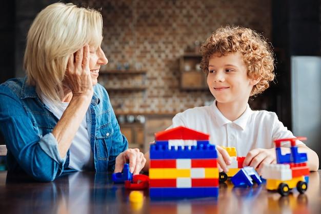 Jongen die met een lichte glimlach naar zijn vrolijke oma kijkt terwijl hij zowel aan een tafel zit als thuis met plastic bouwstenen speelt.