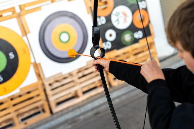 Jongen die met een opleidingsboog streven bij een bullseye bij een markt.