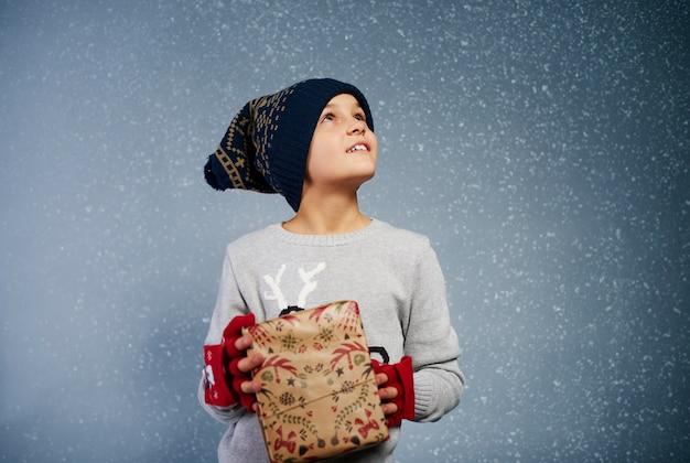 Jongen die met giftdoos sneeuw bekijkt