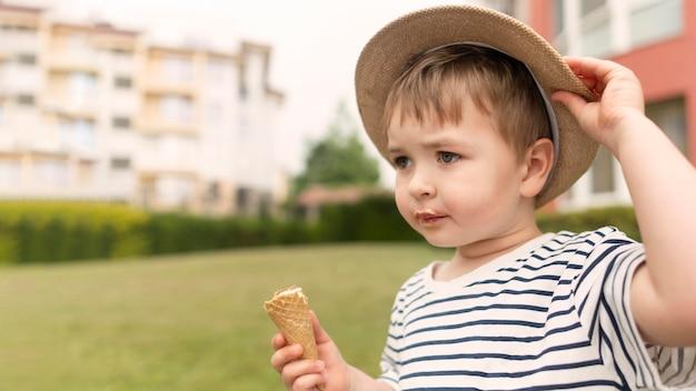 Jongen die met hoed van roomijs geniet