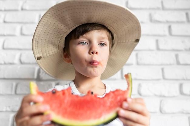 Jongen die met hoed van watermeloen geniet