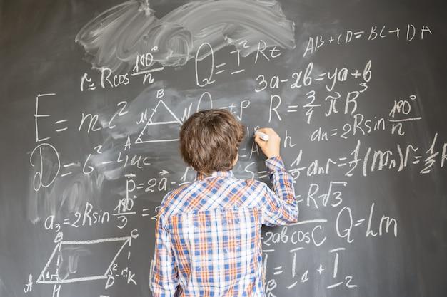Jongen die met krijt op het zwarte bord van wiskundige formules schrijft