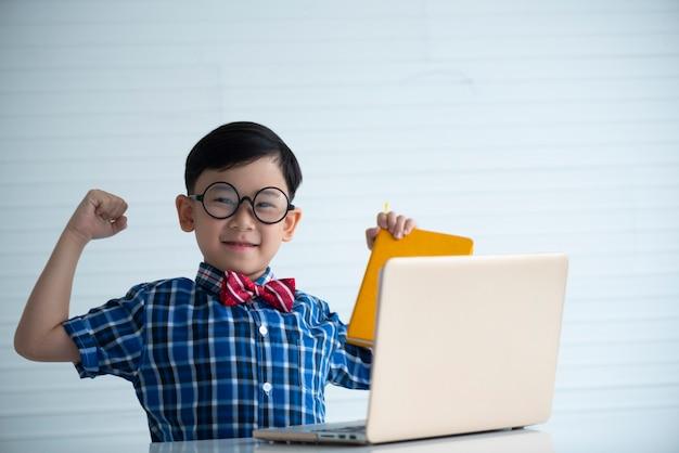 Jongen die met laptop voor het leren glimlacht