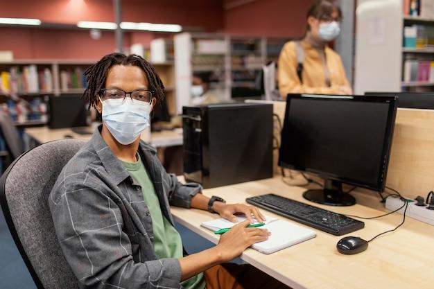 Jongen die met medisch masker in de bibliotheek bestudeert