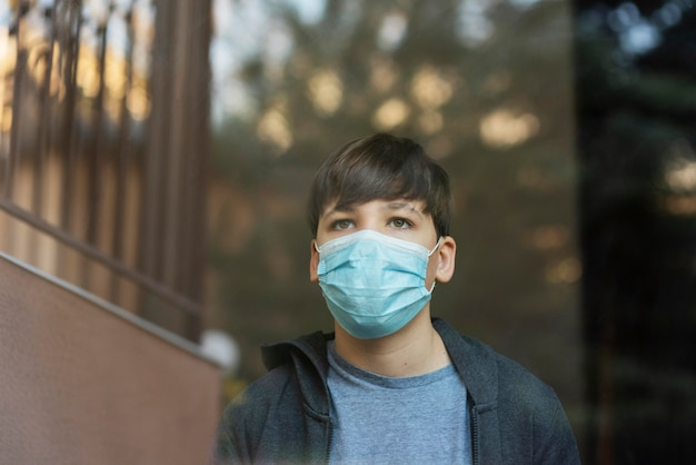 Jongen die met medisch masker naast een raam naar buiten kijkt