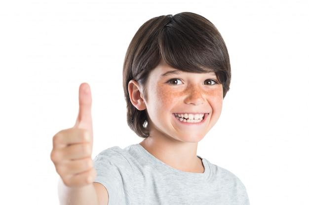 Jongen die met omhoog duim glimlacht