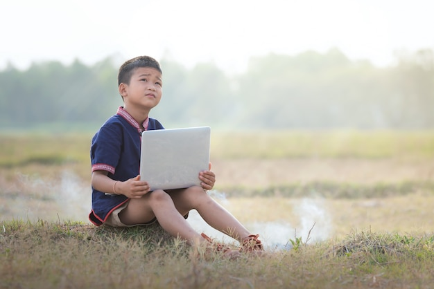Jongen die met online in openlucht het leren met laptops leert.