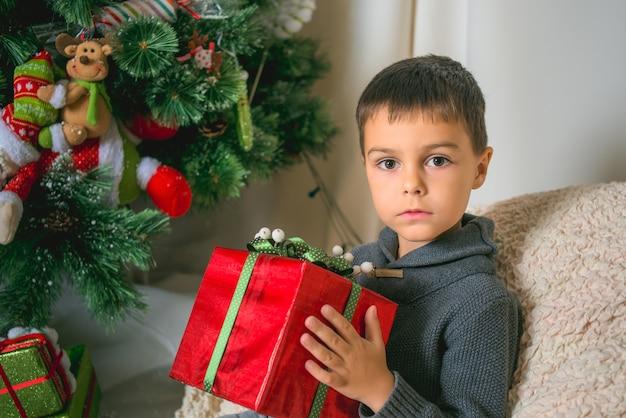 Jongen die met rode gift in zijn handen camera op achtergrond van nieuwjaarboom bekijkt. kerstthema