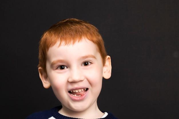 Jongen die met rood haar glimlacht en lacht