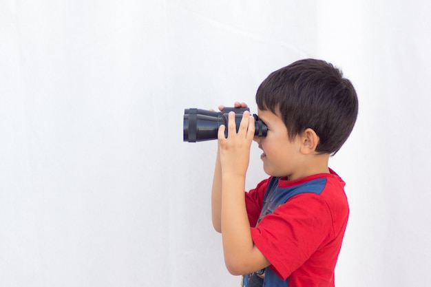 Jongen die met zwarte verrekijker van linkerprofiel met blauw en rood overhemd op witte achtergrond kijkt