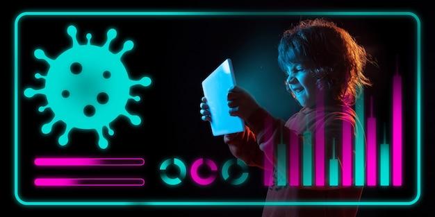 Jongen die moderne interfacetechnologie en digitaal laageffect gebruikt als informatie over de verspreiding van de coronaviruspandemie. analyseren van de situatie met 's werelds telling van gevallen, gezondheidszorg, medicijnen en zaken.