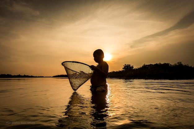 Jongen die op de rivier vist.