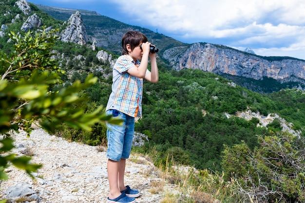 Jongen die op de top van de berg staat en door een verrekijker kijkt kind wandelen op een mooie zomerdag in de franse alpen, rustend op een rots en een geweldig uitzicht op de bergtoppen bewonderen actieve familievakantie